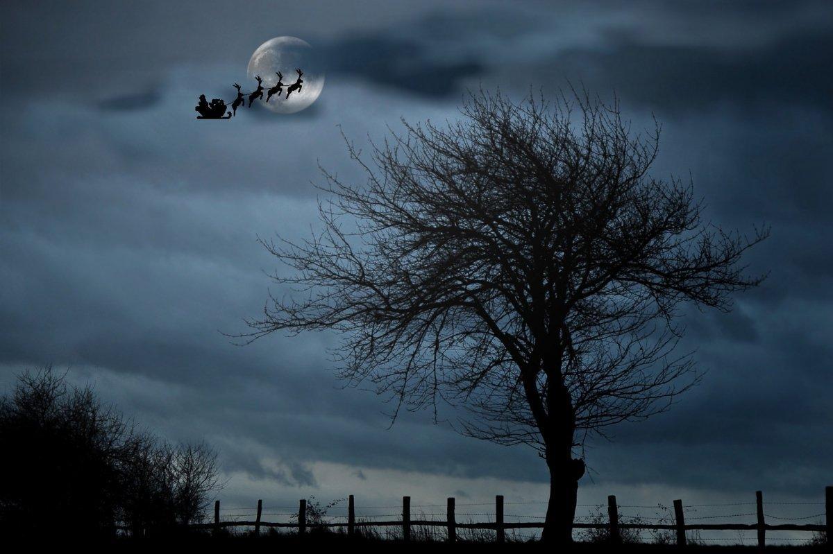 Papá Noel en su trineo y con sus renos surcando los cielos
